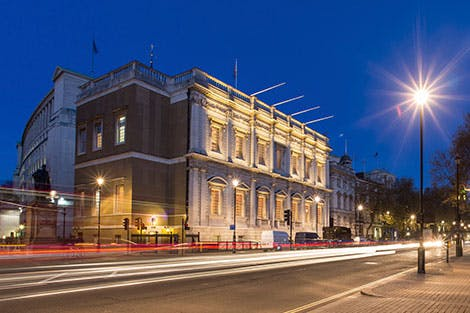 Exterior of Banqueting House at night with Whitehall in the foreground under a clear sky.