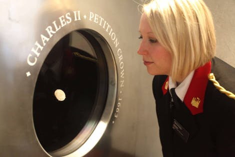 A Tower of London warder looks into a Charles II coin display at the Royal Mint
