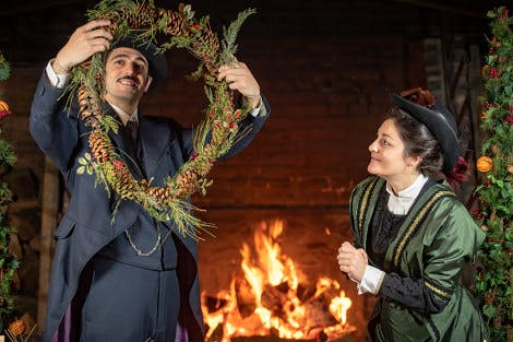 Costumed Interpreters dressed as Edwardian grace and favour residents preparing the palace for the Christmas season with a festive wreath in front of the fire in the Tudor kitchens.