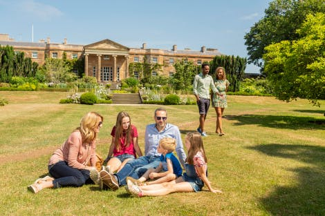 A family consisting of a mum, dad, teenage daughter, young boy and girl relax on the South Lawn with the South Facade of the castle in the background. A young couple are also strolling through the gardens behind them. The family appear to be happily chatting away in the summer sun and the sky is blue with only a hint of clouds. The heavy sunshine casts dark shadows on the grass nearby as the rays hit a nearby mature tree.