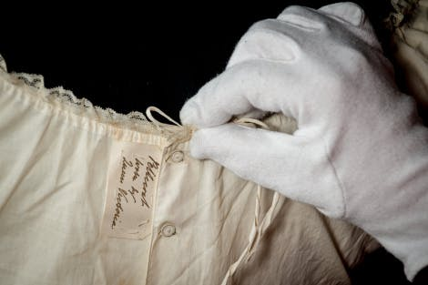 A gloved hand tends to the seam of a cream Victorian petticoat with fine detailing on a black background
