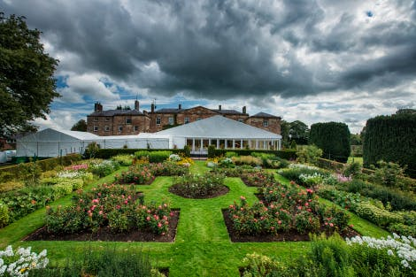 View of a marquee setup on the South Terrace in the grounds of Hillsborough Castle, overlooking the neat and trimmed Granville Garden and overcast with a cloudy sky.