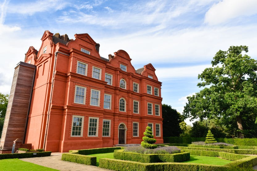 Kew Palace and the palace gardens on a sunny day under a blue partially cloudy sky