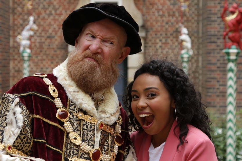 Tracey Tooley investigating Hampton Court Palace with Tudor figures from history.