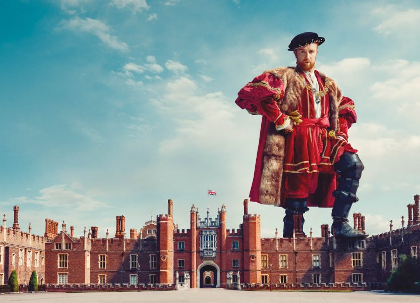 Henry VIII stands above Hampton Court Palace, with a blue sky background.