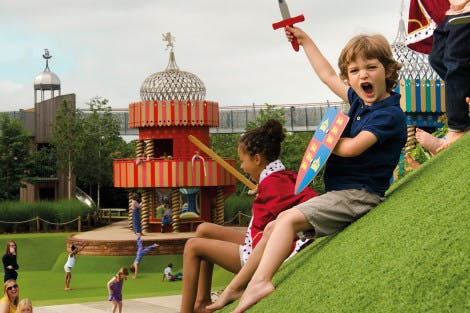 A boy holds up a toy sword and shouts as children play in the background at the Magic Garden at Hampton Court Palace