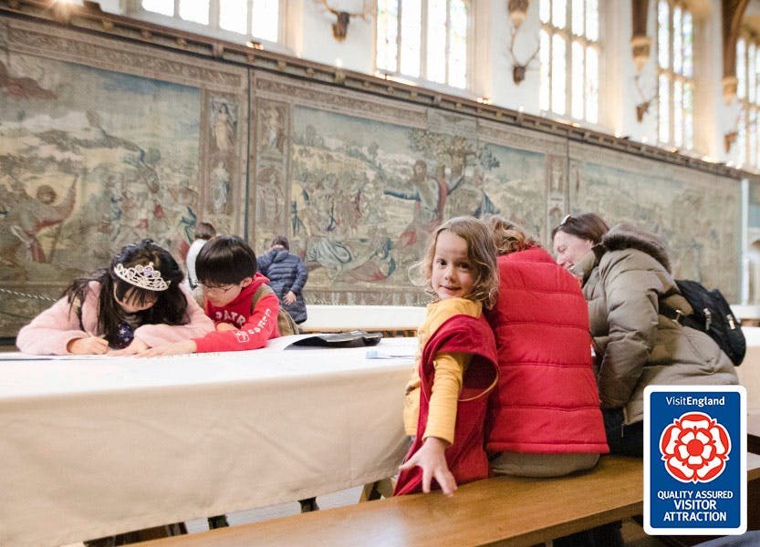 Visitors seated in the Great Hall, working on family activities and surrounded by Tudor tapestries