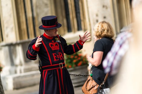 A Yeoman Warder speaks expressively to two visitors as they listen on intently. The Chapel Royal of St Peter ad Vincula can be seen in the background