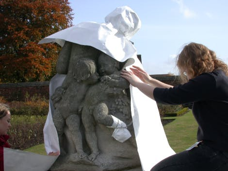Conservator wrapping a statue in the Rose Garden at Hampton Court Palace as part of the annual winter protection programme