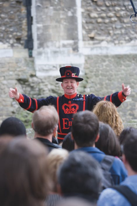 A Yeoman Warder, dressed in navy blue and red ceremonial uniform, giving a guided tour of the Tower of London to a group of visitors