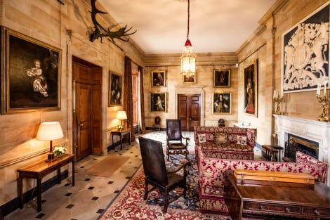 State Entrance of Hillsborough Castle showing fireplace with surrounding seating and furniture. Looking towards doors leading into Candlestick Hall.
