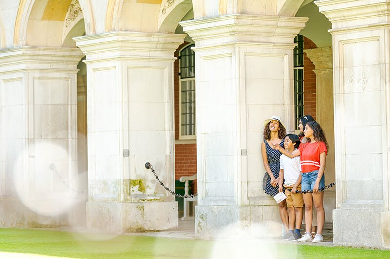 A family of two women, a boy and a girl smile and talk in Fountain Court at Hampton Court Palace