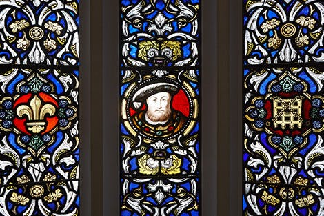 Detail of a stained-glass window showing the heraldry of King Henry VIII, including the Beaufort Portcullis and fleur-de-lis.  In the centre is a likeness of the King.