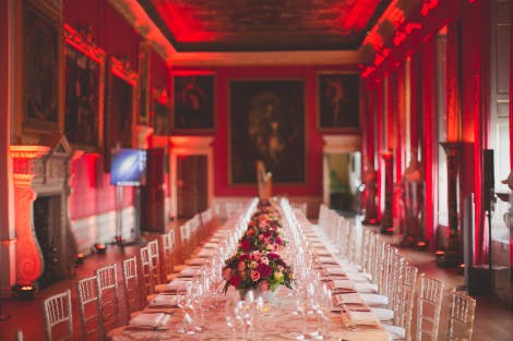 A long table set up for dinner in the State Apartments of Kensington Palace. The walls are bright red and there are paintings hanging on the walls.