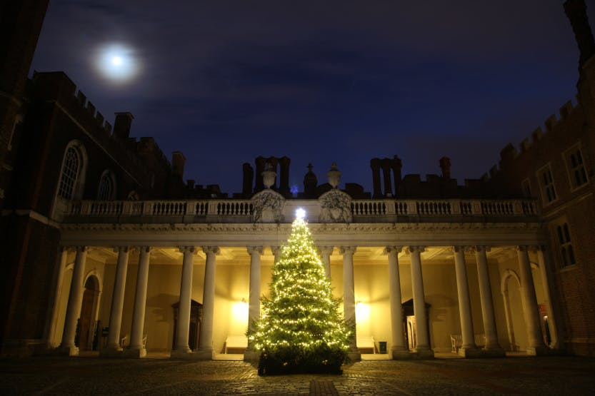 Christmas tree lit up with lights in Clock Court at Hampton Court Palace at twilight