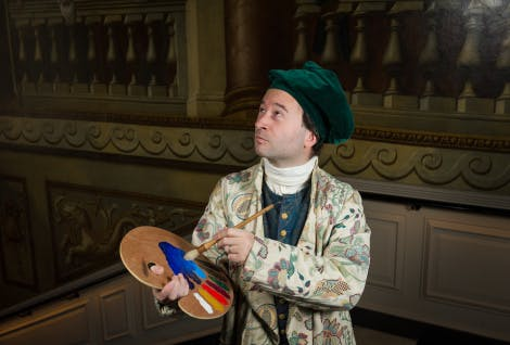 A costumed interpreter dressed as a Georgian painter