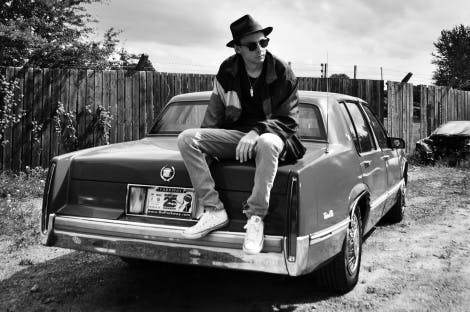 Image of jazz percussionist David Lyttle sat on a car bonnet