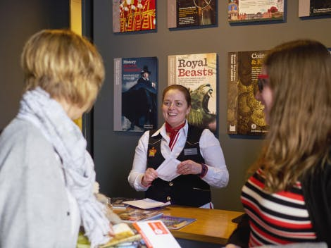 A female member of the Admissions staff in uniform stands behind a desk while speaking to two female visitors.