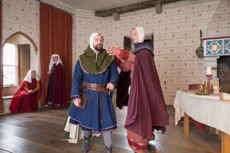 Two medieval knights in civilian clothes talking in the Medieval Palace. In the background, two medieval ladies are in conversation.
