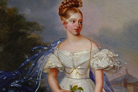 Full-length, standing, facing the viewer, head turned half to the right, wearing a white dress with a diaphanous blue wrap, holding a posie of flowers in her right hand; beside a path in a parkland setting, with Kensington Palace in the distance, on the right.