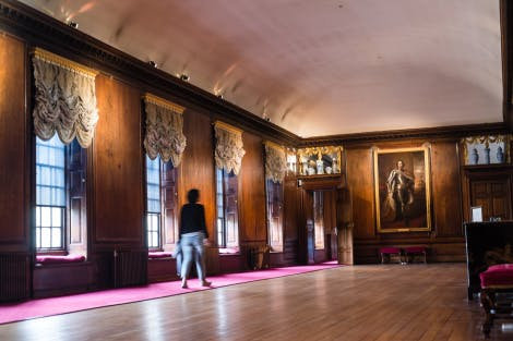 A visitor makes her way through the brown wooden interiors of the Queen's Gallery. A large portrait and collection of fine ceramics adorn the walls