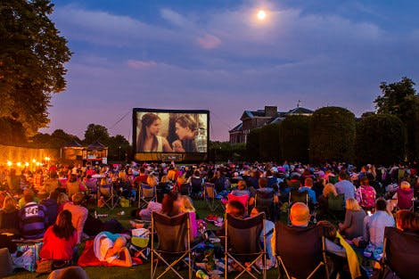 View of Kensington Palace with crowd in the foreground and a Luna Cinema screen in the background showing Romeo and Juliet.