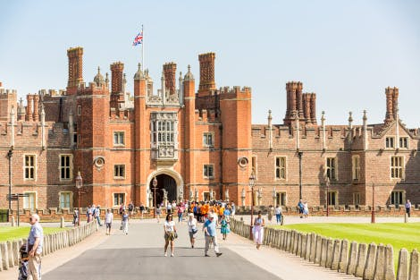 Tudor West Gate of Hampton Court Palace under a blue sky. Visitors can be seen in the foreground