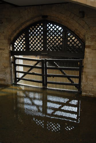 Traitors' Gate: barred, closed, gate with water in front of it.
