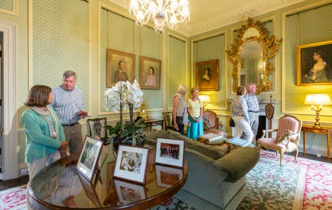 A group of visitors wander around Lady Grey's Study, the last room on the tour of Hillsborough Castle. A crystal chandelier hangs above the room which features a soft teal wallpaper, hand-block printed with a flower design. A large ornate gold mirror hangs above a white marble fire place and painted portraits of the royal family and Hills family hang on the walls. The room also features comfy sofas and chairs. A round table with white orchid is visible in the foreground.