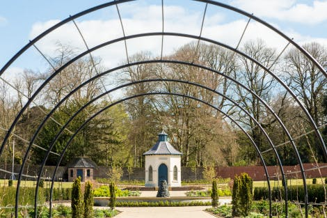 The Walled Garden at Hillsborough Castle and Gardens, showing the pergola in the distance surrounded by planting and bedding. An archway surrounds the frame of the image and there is a blue cloudy sky
