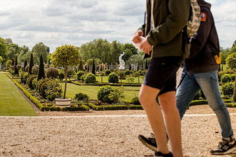 Visitors walking through the Privy Garden at Hampton Court Palace