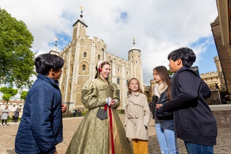 Actress dressed in Tudor costume talking to family group at the Tower of London