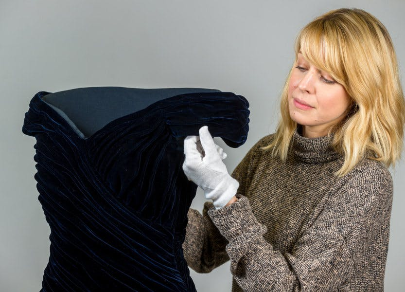 A HRP conservator works on a midnight blue silk velvet evening dress designed by Victor Edelstein (1985), also known as the 'Travolta dress'.