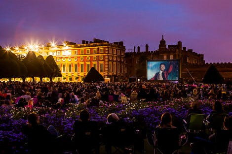 View of Hampton Court Palace with crowd in the foreground and Luna Cinema screen showing The Greatest Showman in the background.