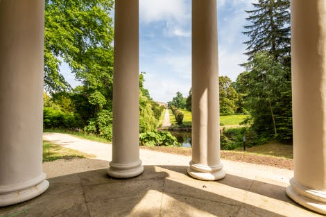 Lady Alice's Temple, looking east from inside the temple towards Yew Tree Walk. The stone floor of the temple and four of the columns are in the foreground. The pond and Yew Tree Walk are seen in the background.   The domed temple was given as a wedding gift to Lady Alice Hill by her brother, the 5th Marquess of Downshire in 1867. A circular seat inside the temple sits behind a screen of Ionic columns.