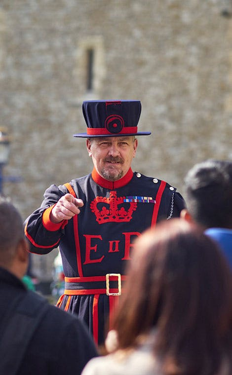 A Yeoman Warder also known as a 'Beefeater' is shown giving a tour to a group of visitors.