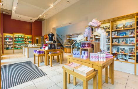 The Main Tower Shop, looking south-west. Showing displays of merchandise, including Historic Royal Palaces branded chocolate and other foodstuffs, t-shirts and books. Stairs leading up to the first floor for children's books and games can be seen in the background.