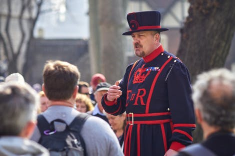 A Yeoman Warder in full uniform giving a tour of the Tower of London to a group of visitors. Tudor and medieval buildings can be seen in the background