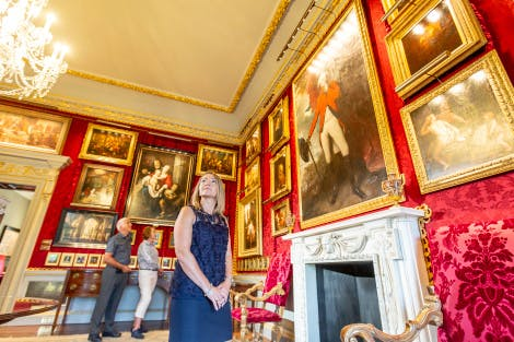 A lady stands in a Georgian room, looking around her at the gold-framed paintings adorning the Red Room. The walls are covered in deep red silk damask and a marble fireplace is visible. An older couple can be seen in the background, also looking at the paintings.