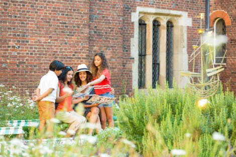 A family of two women, a boy and a girl look around them in the Chapel Court of Hampton Court Palace
