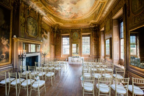Wedding ceremony set up in a room in a heritage building under a painted ceiling and surrounded by art
