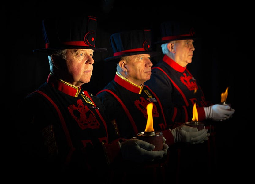 Three Yeoman Warders stand holding flames in front of a black background