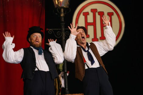 Two actors dressed in historical costume throw up their hands in horror during a Horrible Histories performance. The Horrible Histories logo appears in the background as part of the red and black set.