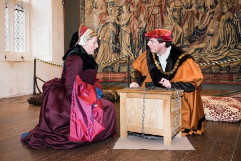 A live interpreter dressed as a Tudor Lady and a Live Interpreter dressed as a Tudor Gentlemen are kneeling on either side of a padlocked chest in the Great Watching Chamber. They are arguing.