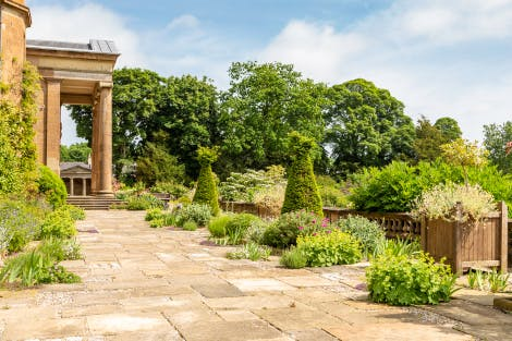 The South Terrace, looking south-east across the terrace flagstones towards the small topiary trees and summer shrubs. The Greek Temple is just seen through the castle portico in the background on the left of the image.