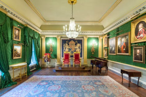 Throne Room with silk green damask walls, wooden floor and large rug. Two red and gold Chairs of State, or 'thrones' are situated at the far end of the room. Gold-framed paintings of landscapes adorn the walls and three large chandeliers hang above.