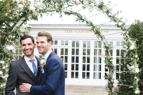 Two grooms in dark blue suits stand under an archway decorated with flowers, in front of an events venue labelled the Garden Room