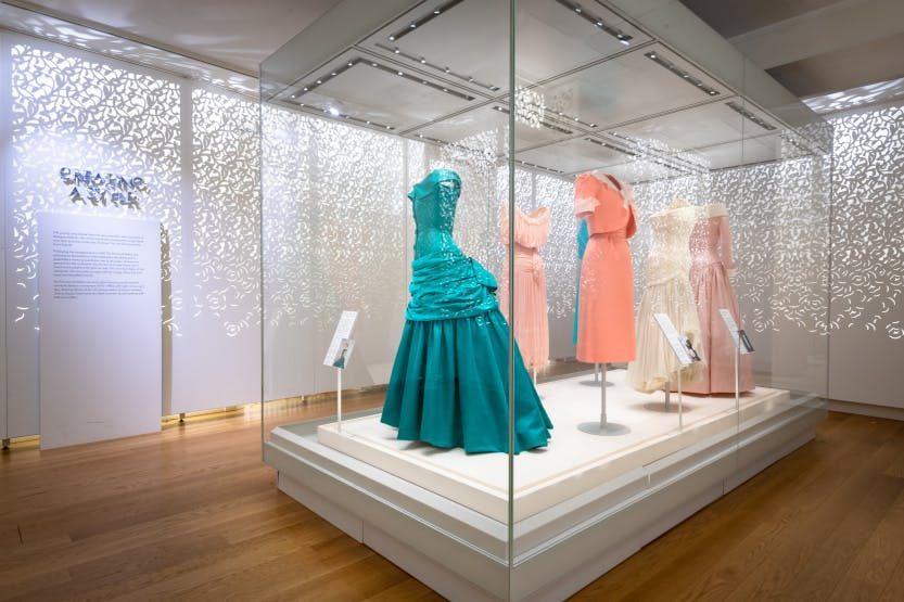 Bright turqiose and pale pink dresses on display in a bright white room as part of the Diana: Her Fashon Story exhibition