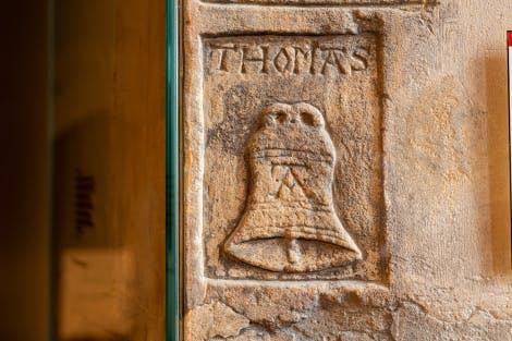 Thomas Abel's graffiti in the Beauchamp Tower - Imprisonment at the Tower display and exhibition at the Tower of London. The carving shows a large bell with an 'A' on the front, with the name 'Thomas' carved above it.