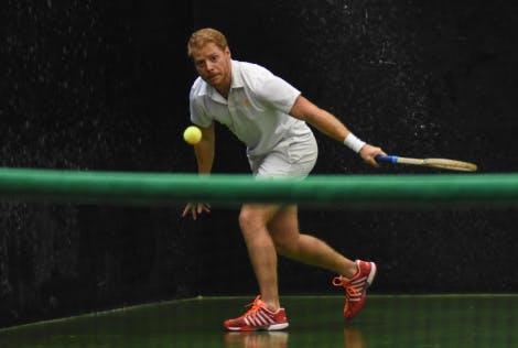 A real tennis player hits a ball across a green tennis court